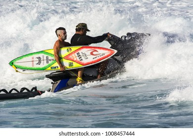 NORTH SHORE, OAHU, HAWAII - JANUARY 11, 2018: The Hawaiian Water Patrol gives an unidentified surfer a ride out to sea to catch big waves at the Banzai Pipeline.
