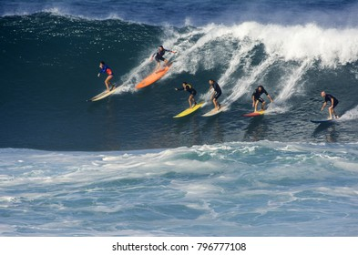 NORTH SHORE, OAHU, HAWAII - JANUARY 14, 2018: Six unidentified surfers catch a big wave at Waimea Bay Beach Park located on the North Shore of Oahu.