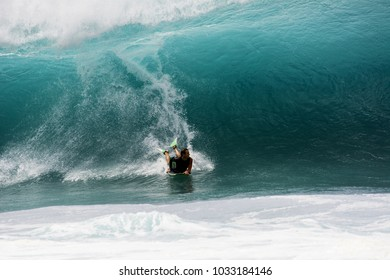 NORTH SHORE, OAHU, HAWAII - MARCH 26, 2017: An unidentified body boarder catches a big wave at the Banzai Pipeline located on the North Shore of Oahu.