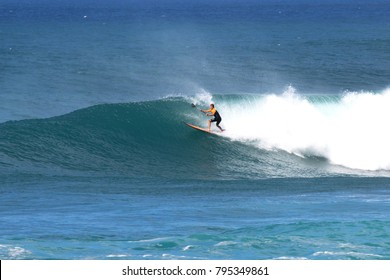 North Shore, Oahu, Hawaii / USA - January 18, 2018: A stand-up paddle surfer riding waves at Sunset beach on a sunny day