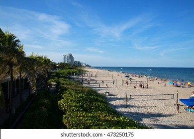 North Side of Deerfield Beach, Florida with Beachgoers Sunbathing and Enjoying Activities, Volleyball Nets Lower Right, Green Foliage Lower Left, Sunny Afternoon with Wispy Clouds in the Spring