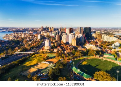 North Sydney from St LEonards park and Oval to distant city CBD across Sydney harbour on a sunny morning under blue sky - aerial elevated view.