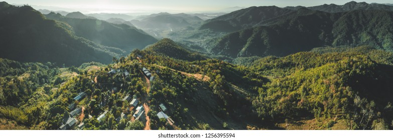 North Thailand wild nature. Aerial drone shot of mountain valley with green covered hills. Overwhelming Asian landscape. Buildings among the wild environment.