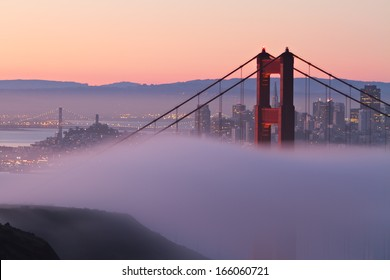 The north tower of the Golden Gate Bridge draped in morning fog with beautiful San Francisco in the background.