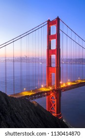 The north tower of the iconic Golden Gate Bridge stands tall backed by the city of San Francisco just before sunrise.