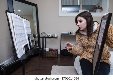 NORTH VANCOUVER, BC, CANADA - APR 16, 2020: A young woman adapting to self isolation during the Covid 19 pandemic by teaching students from home.