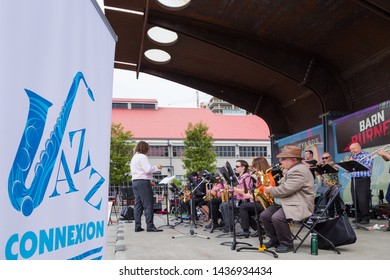 NORTH VANCOUVER, BC, CANADA - JUNE 9, 2019: A jazz band ensemble playing woodwind and brass instruments with a conductor at a live concert performance at North Vancouver's Lonsdale Quay.