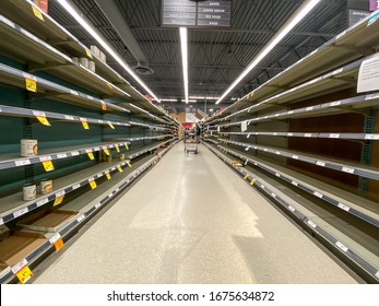 NORTH VANCOUVER, BC, CANADA - MAR 15, 2020: Shelf at a supermarket mostly empty with only a few packages of toilet paper left amid panic buying as the coronavirus spreads.