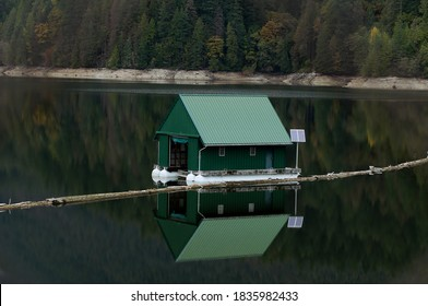 NORTH VANCOUVER, BC/CANADA-10/17/2020: Closer view of Capilano reservoir green boathouse with reflection on the water.