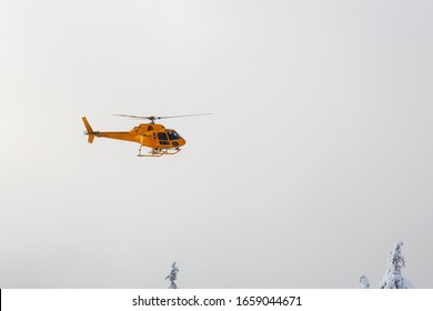 North Vancouver, British Columbia, Canada - February 17, 2020: North Shore Search and Rescue Helicopter is flying to aid a man skier in the backcountry of Seymour Mountain during winter evening.