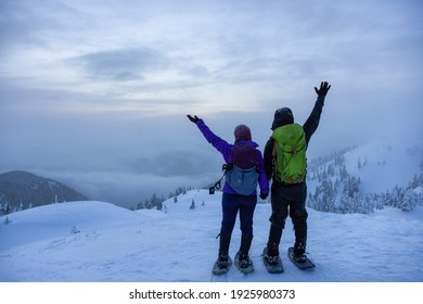 North Vancouver, British Columbia, Canada - February 13, 2021: Adventurous Couple on top of Seymour Mountain during snowy winter sunset.