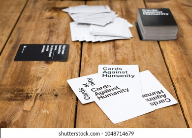 NORTH VANCOUVER, CANADA - MARCH 9, 2018: Cards Against Humanity, A party game for horrible people, displayed on a wooden table.