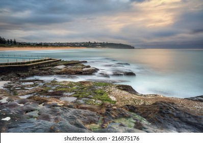 North view overlooking coast and rock pool at South Curl Curl. Australia.  Motion in water, clouds and railings
