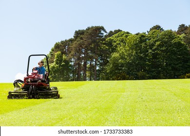 North Wales UK - May 21, 2014: Gardner on ride on lawn mower, concept lawn mower cutting grass with gardening tool.