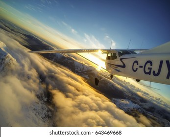 North West from Vancouver, British Columbia, Canada - March 30 2017 - Outside the airplane perspective of a small Cessna 172 flying around the mountains during sunset.