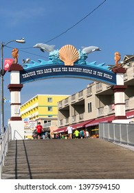 """North Wildwood, New Jersey / United States - July 23 2018 : the Wildwood boardwalk arch entrance on a hot sunny morning Stating """"Through this arch walk the happiest people in the world """" which is true"""