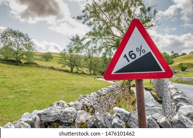 North Yorkshire, UK - Circa August 2019: Detailed view of a red warning roadside triangle showing a 16% steep gradient, seen in a rural area of the Yorkshire Dales. Rolling hills can be seen.