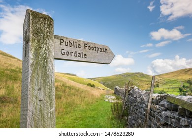 North Yorkshire, UK - Circa August 2019: Shallow focus of a wooden public footpath sign seen at the heart of the Yorkshire Dales. A stone wall is seen leading to a hilly region in the background.