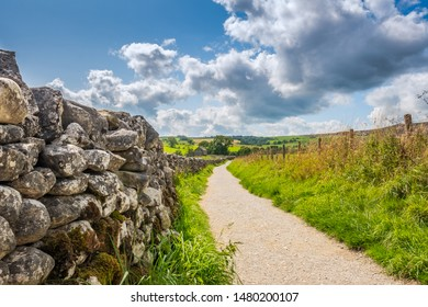 North Yorkshire, UK - Circa August 2019: Low level view of a very old, stone wall seen extending to an abandoned farmhouse in the distance. A single track path leads the way, part of a footpath.