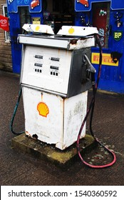 North Yorkshire / UK - July 2018: An old petrol pump dispensing Shell petrol standing on a forecourt with royal blue painted workshop doors in the background. The Shell logo is visible on the pump.