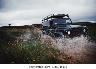 North Yorshire Moors, UK - July 23 2020: A Land Rover Defender off roading on a green lane in the North Yorkshire Moors in England.