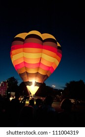 NORTHAMPTON, ENGLAND - AUGUST 18: Hot Air Balloon glowing brightly for night show at the Northampton Balloon Festival, on August 18, 2012 in Northampton, England.