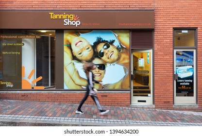 Northampton, Northamptonshire / UK - November 13th 2018: Tanning Shop outlet on Wellington Street. A person, blurred for artistic purposes, walks in front of it down a slope.
