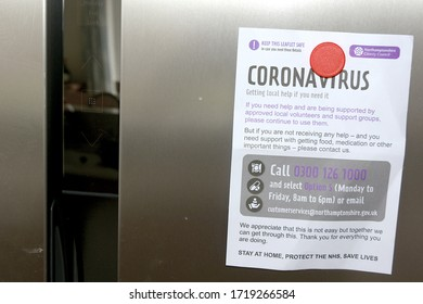 Northamptonshire, England/ United Kingdom - May 1 2020: A leaflet published by Nothamptonshire County Council advertising help during the coronavirus Covid-19 pandemic on a family's fridge