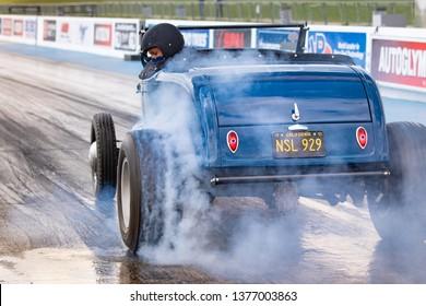 Northamptonshire, UK, Santa Pod Raceway, April 13 2019. VHRA Vintage Hot Rod Association, Vintage Nationals. Spinning wheels and burning rubber from a vintage hot rod in the staging area of drag strip