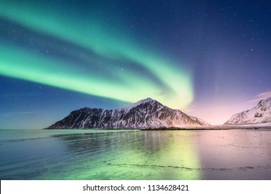 Northen light above mountains and ocean shore. Beautiful natural landscape in the Norway