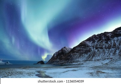 Northen light above mountains and ocean. Beautiful natural landscape in the Norway