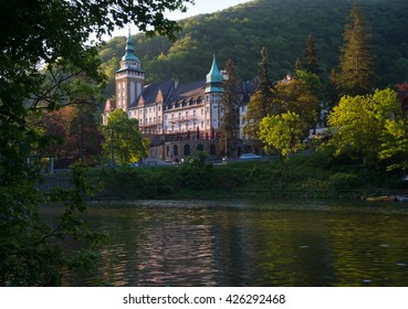 Northern front of Lillafured palace (Miskolc, Hungary). Lake Hamori in foreground, mountains covered with multicolored forest - background.