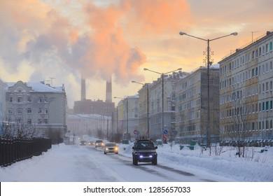 Northern industrial city. Sunset. Smoke from the chimney is visible above the houses. Bogdan Khmelnitsky Street. Norilsk, Krasnoyarsk region, Siberia, Russia.