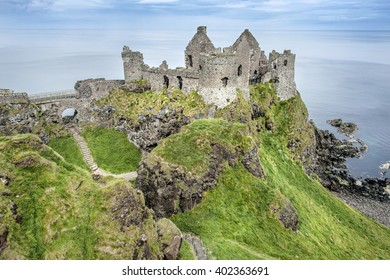 Northern Ireland, near Portrush: The famous old beautiful ruin of Dunluce Castle on green rocky hill with cliff coastline water ocean sea blue sky in the background.