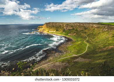 Northern Ireland shoreline overview. Breathtaking Irish landscape. The grass covered land next to the ocean. Tourist trail for hiking in the national park. Blue cloudy sky background. Horizon view.