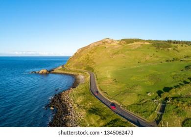 Irlande du Nord, Royaume-Uni. Causeway Coastal Route alias Antrim Coast Road près de Ballygalley Head et de la station balnéaire avec des voitures rouges. Une des routes côtières les plus pittoresques d'Europe. Vue aérienne.