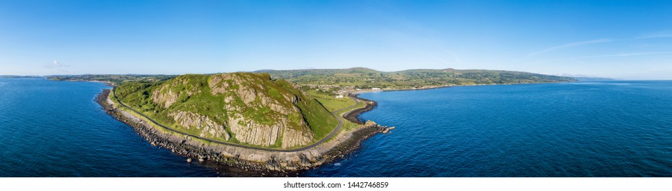 Northern Ireland, UK. Wide aerial panorama of Ballygalley Head mountain and Causeway Coastal Route a.k.a Antrim Coast Road between Larne and Ballygalley. One of the most scenic coastal roads in Europe
