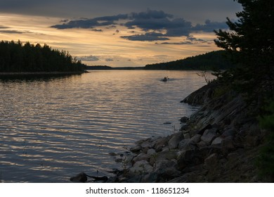 Northern lake under colorfull evening sky, high rocky shore, small touristic kayak paddling back in the distance