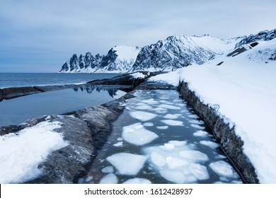 Northern landscape - ice blocks in water tank beside Arctic Ocean and Norwegian Sea on Lofoten Islands at background of notched mountain rocks. Scene in cold blue tones. True winter in North.