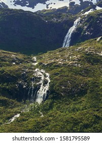 Northern landscape with mountains and forest at the foreground and mountain peak and waterfall on the background. Senja Island, Troms County, Norway.