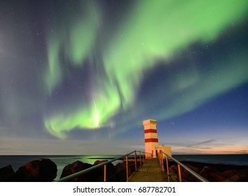 Northern light is above an old lighthouse of Gardur in southwestern Iceland which stands alone at seaside of the North Atlantic Ocean.