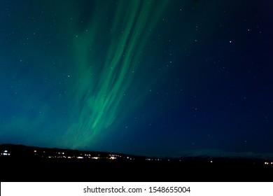 Northern light (aurora borealis) with city foreground