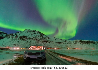 The northern light or Aurora Borealis dancing over mountain with SUV car in Iceland.