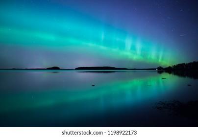 Northern light dancing over calm lake in Farnebofjarden national park in Sweden