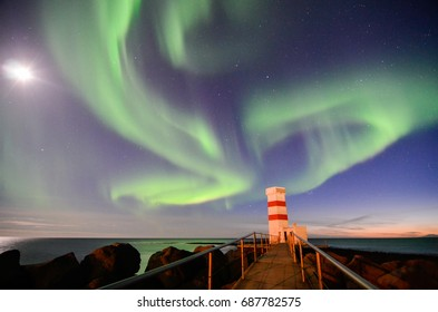 Northern light and the moon are above an old lighthouse of Gardur in southwestern Iceland which stands alone at seaside of the North Atlantic Ocean.
