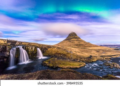 Northern Light over Kirkjufell, Grundarfjordur town, West Iceland with small dark cloud cover the mountain