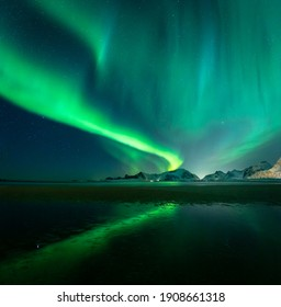 Northern Lights above mountains on Lofoten Islands. Reflections of Aurora Borealis on Sandbotnen sandy beach. Beautiful winter time conditions in northern Norway.