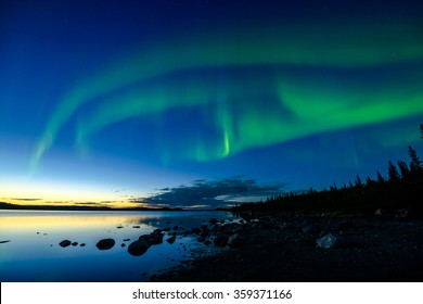 Northern Lights After Sunset - Bands of Northern Lights appear above a rocky lake right after the sun sets.