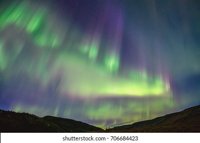 northern lights appear in cloudless, starry night sky over moose creek and ridge in denali national park, alaska