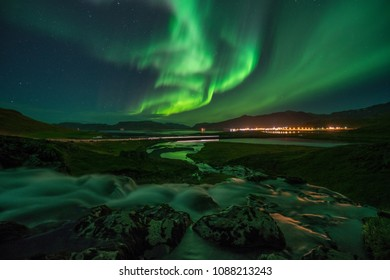 Northern lights (Aurora Borealis) above a small town in Iceland